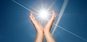 image of raised hands cupped around sunlight